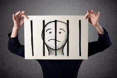 Homem de negócios que guarda um papel com um prisioneiro atrás das barras sobre mim Imagens de Stock Royalty Free