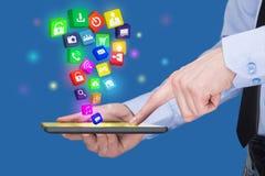 Homem de negócios que guarda um PC da tabuleta com ícones móveis das aplicações na tela virtual Internet e conceito do negócio imagem de stock