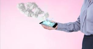 Homem de negócios que guarda um smartphone que projeta holograma contra o fundo cor-de-rosa Fotografia de Stock