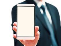 Homem de negócios que guarda um telefone em sua mão telefone esperto com a tela vazia para ideias do conceito Imagem de Stock