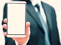 Homem de negócios que guarda um telefone em sua mão telefone esperto com a tela vazia para ideias do conceito Imagens de Stock