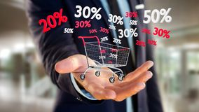 Homem de negócios que guarda um trole e um disconto vermelhos e brancos das vendas - Imagem de Stock