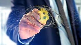 Homem de negócios que guarda um voo cripto do sinal de moeda de Bitcoin ao redor Fotos de Stock Royalty Free