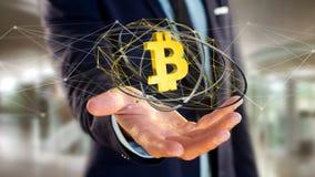 Homem de negócios que guarda um voo cripto do sinal de moeda de Bitcoin ao redor Foto de Stock
