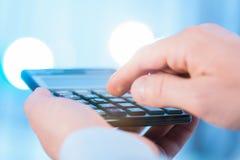 Homem de negócios que guarda uma calculadora e uma contagem imagem de stock