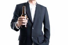Homem de negócios que guarda uma garrafa de cerveja no fundo branco isolado foto de stock