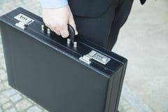 Homem de negócios que guarda uma mala de viagem fotografia de stock royalty free
