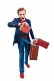 Homem de negócios que guarda uma mala de viagem ao olhar seu relógio Fotos de Stock Royalty Free
