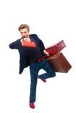 Homem de negócios que guarda uma mala de viagem ao olhar seu relógio Foto de Stock Royalty Free