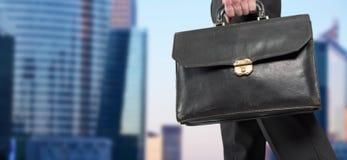 Homem de negócios que guarda uma pasta com prédios de escritórios no fundo Imagens de Stock Royalty Free
