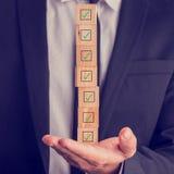 Homem de negócios que guarda uma pilha de caixas verificadas Imagem de Stock