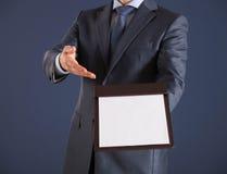 Homem de negócios que guarda uma prancheta com a folha de papel vazia Imagens de Stock