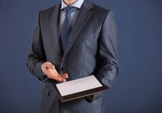 Homem de negócios que guarda uma prancheta com a folha de papel vazia Fotos de Stock Royalty Free