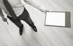 Homem de negócios que guarda uma prancheta com a folha de papel vazia Foto de Stock Royalty Free