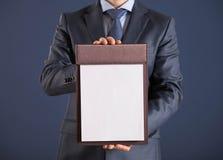 Homem de negócios que guarda uma prancheta com a folha de papel vazia Fotografia de Stock