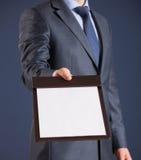 Homem de negócios que guarda uma prancheta com a folha de papel vazia Fotografia de Stock Royalty Free
