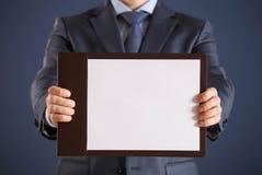 Homem de negócios que guarda uma prancheta com a folha de papel vazia Imagem de Stock