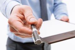 Homem de negócios que guarda uma prancheta com a folha de papel vazia e o PR Imagem de Stock Royalty Free