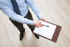 Homem de negócios que guarda uma prancheta com a folha de papel vazia e o PR Imagem de Stock
