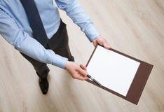 Homem de negócios que guarda uma prancheta com a folha de papel vazia e o PR Imagens de Stock