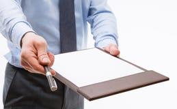 Homem de negócios que guarda uma prancheta com a folha de papel vazia e o PR Imagens de Stock Royalty Free