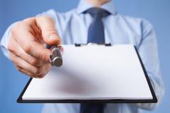 Homem de negócios que guarda uma prancheta com a folha de papel vazia e o PR Fotografia de Stock Royalty Free