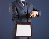 Homem de negócios que guarda uma prancheta com placa e que indica a Foto de Stock