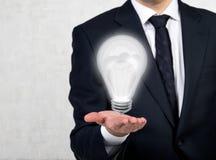 Homem de negócios que guardara a lâmpada Imagens de Stock Royalty Free