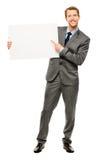 Homem de negócios que guardara o cartaz branco vazio que mostra o espaço da cópia imagem de stock royalty free