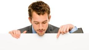 Homem de negócios que guardara o cartaz branco vazio que mostra o espaço da cópia fotografia de stock