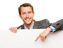 Homem de negócios que guardara o cartaz branco vazio que mostra o espaço da cópia foto de stock