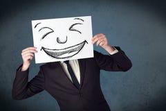 Homem de negócios que guardara um papel com a cara do smiley na frente de seu hea Fotos de Stock