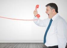 Homem de negócios que guardara um telefone e que grita Foto de Stock