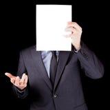 Homem de negócios que guardara uma folha de papel vazia na frente de sua cara Fotografia de Stock Royalty Free