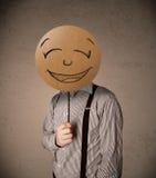 Homem de negócios que guardara uma placa da cara do smiley Foto de Stock Royalty Free