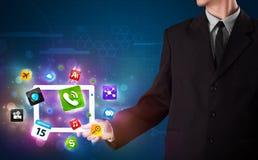 Homem de negócios que guardara uma tabuleta com apps e ícones coloridos modernos Imagens de Stock