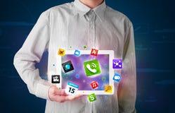 Homem de negócios que guardara uma tabuleta com apps e ícones coloridos modernos Fotos de Stock Royalty Free