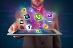 Homem de negócios que guardara uma tabuleta com apps e ícones coloridos modernos Fotografia de Stock