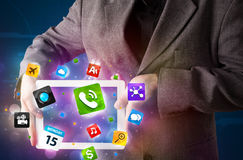Homem de negócios que guardara uma tabuleta com apps e ícones coloridos modernos Foto de Stock