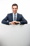 homem de negócios que inclina-se em um cartaz branco Imagens de Stock Royalty Free