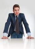 Homem de negócios que inclina-se em uma mesa Imagem de Stock Royalty Free