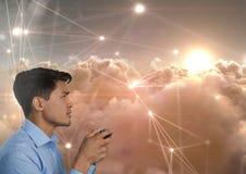 Homem de negócios que joga com o controlador do jogo de computador com linha conexões da luz no fundo das nuvens Imagem de Stock