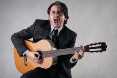 Homem de negócios que joga a guitarra Fotografia de Stock