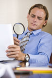 Homem de negócios que lê a cópia fina no contrato Foto de Stock Royalty Free