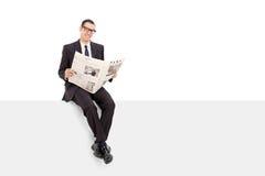 Homem de negócios que lê a notícia assentada em um painel Imagem de Stock Royalty Free