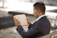 Homem de negócios que lê seu jornal Fotos de Stock
