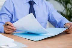 Homem de negócios que lê um contrato antes de assiná-lo Imagem de Stock