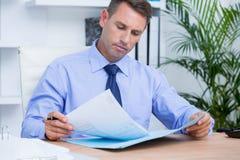 Homem de negócios que lê um contrato antes de assiná-lo Fotografia de Stock