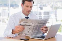 Homem de negócios que lê um jornal fotos de stock