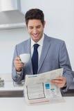 Homem de negócios que lê um jornal e que bebe um café foto de stock royalty free